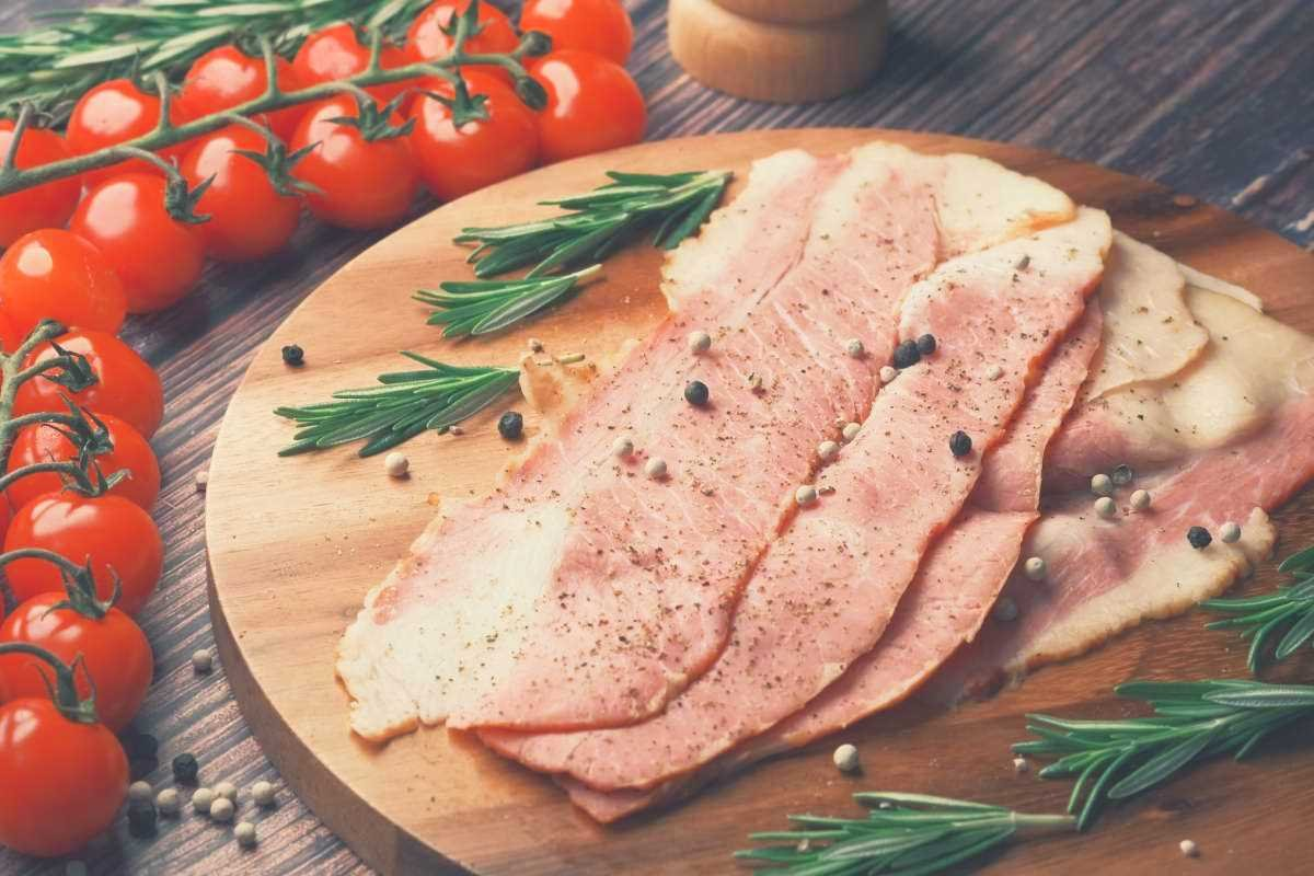 Slices of country ham on a wooden board, surrounded by tomatoes on the vine