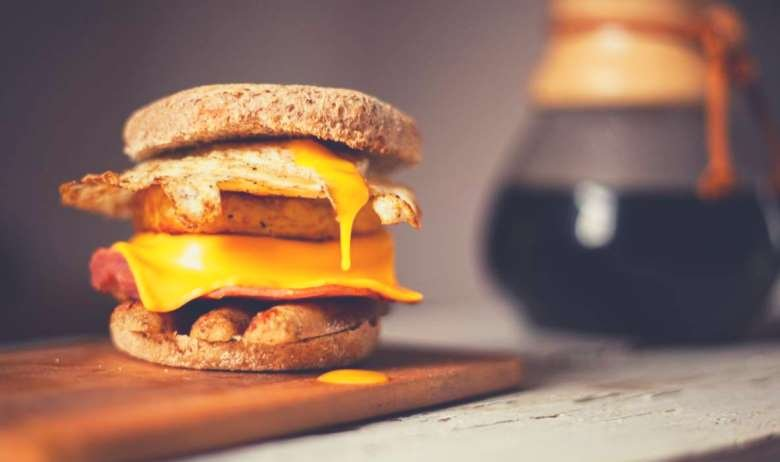A sausage patty, cheese and fried egg in a muffin, next to a glass carafe of coffee