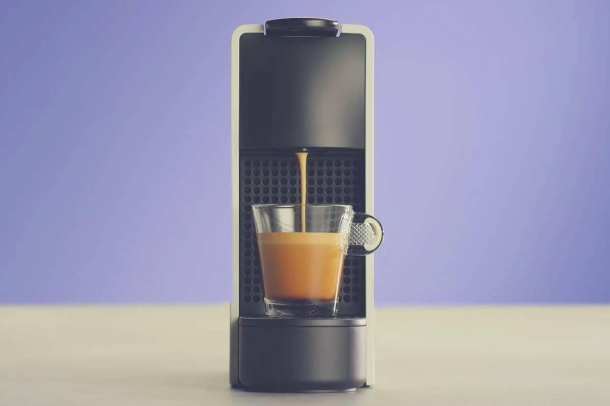 A Nespresso Essenza Mini coffee maker on a kitchen worktop against a blue background