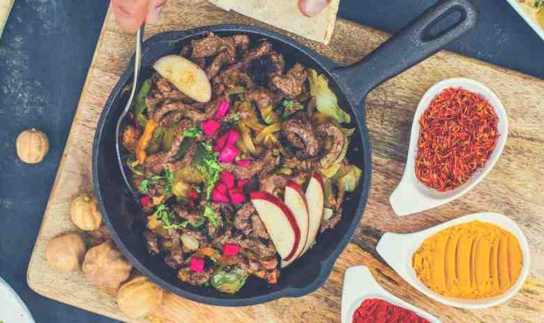 A skillet of meat, fruit and vegetables being served alongside three spices