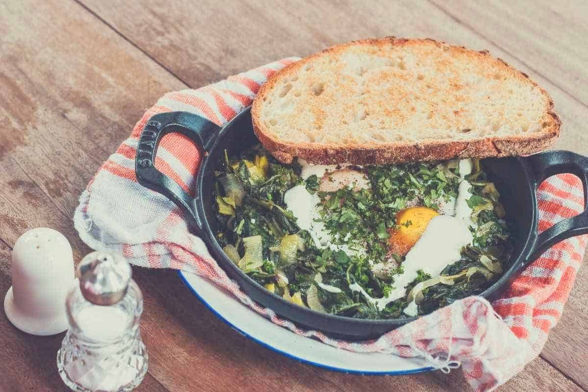 An egg and greens meal served in a skillet with a piece of toast. Salt and pepper shakers are next to it